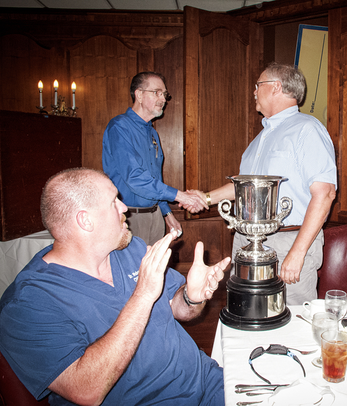 Ray Bordelon (left) presents David Friedrichs with the Kiwanis of the Year trophy that is passed along each year.